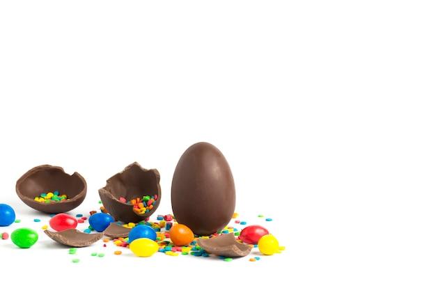 Huevo de pascua de chocolate entero y roto y dulces multicolores en un blanco. concepto de celebrar la pascua. copia espacio