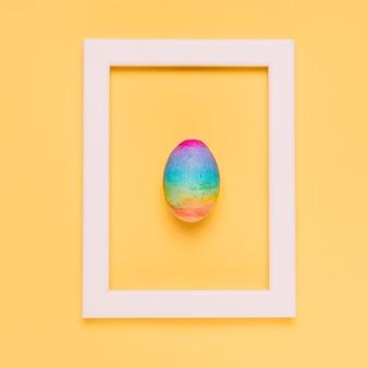 Huevo de pascua del color del arco iris dentro del marco blanco de la frontera en fondo amarillo