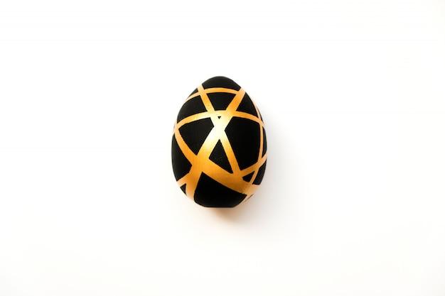 Huevo de pascua dorado con patrón geométrico negro aislado sobre fondo blanco