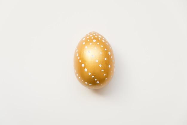 Huevo de pascua dorado con puntos aislados sobre fondo blanco