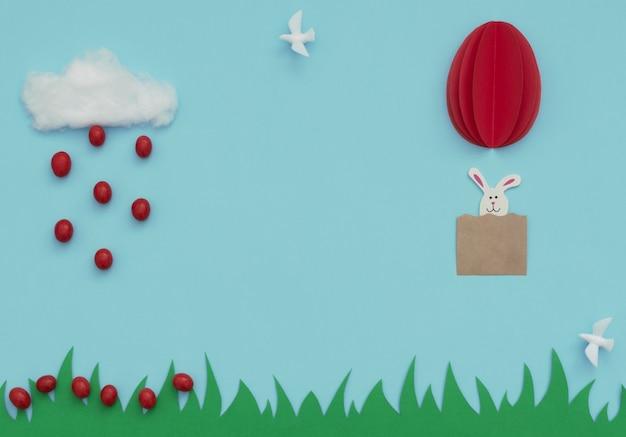 Huevo de pascua globo de aire caliente hecho de papel con conejito y nube de algodón con lluvia de pequeños huevos de pascua rojos cayendo sobre la hierba en azul