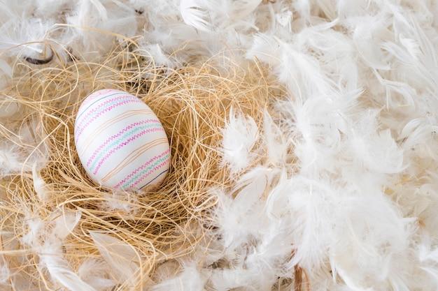 Huevo de pascua en heno entre montón de plumas