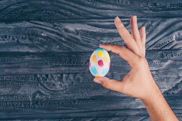 Huevo de pascua con hombre sosteniendo en la mano sobre fondo de madera oscura.