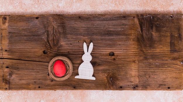Huevo de pascua en nido con conejo en mesa