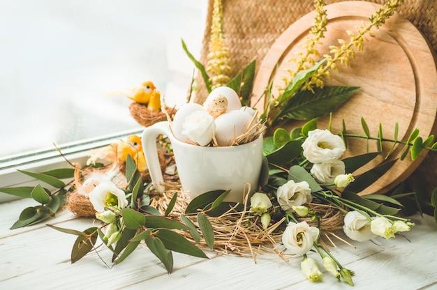 Huevo de pascua en un nido con decoración floral cerca de la ventana. huevos de codorniz. feliz, pascua, concepto