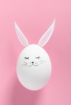 Huevo de pascua con orejas de conejo y cara sobre fondo rosa con espacio de copia. endecha plana. concepto mínimo. foto creativa conceptual acerca de felices vacaciones de pascua.