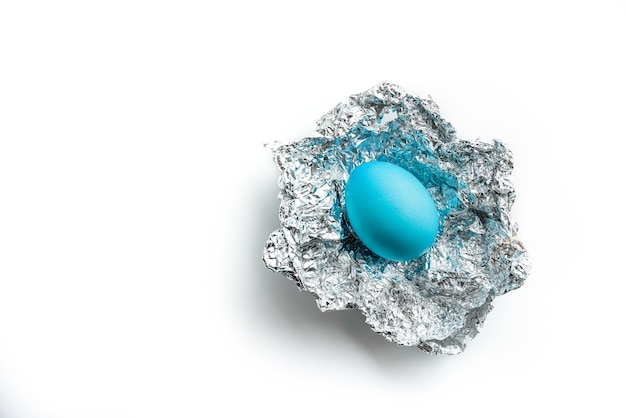 Huevo de pascua en papel de plata sobre un fondo blanco con espacio de copia. concepto de regalo de pascua.