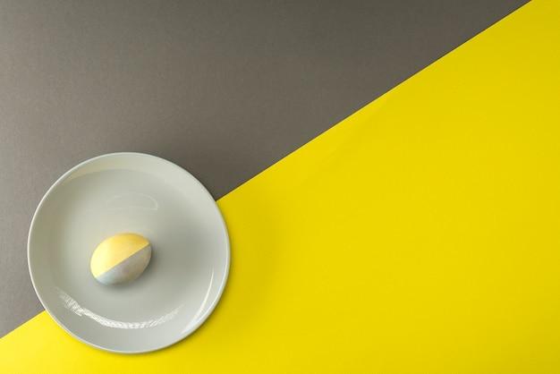 Huevo de pascua pintado de amarillo-gris en una placa gris sobre una superficie amarillo-gris con un lugar para el texto