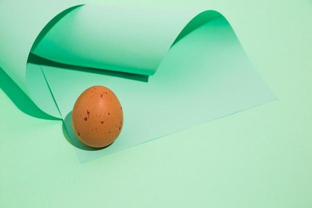 Huevo pequeño de gallina marrón con papel enrollado.