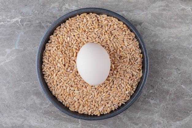 Huevo y pila de cebada en placa negra.