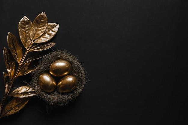 El huevo está pintado de oro en un nido de paja y la planta con hojas doradas sobre una mesa negra.