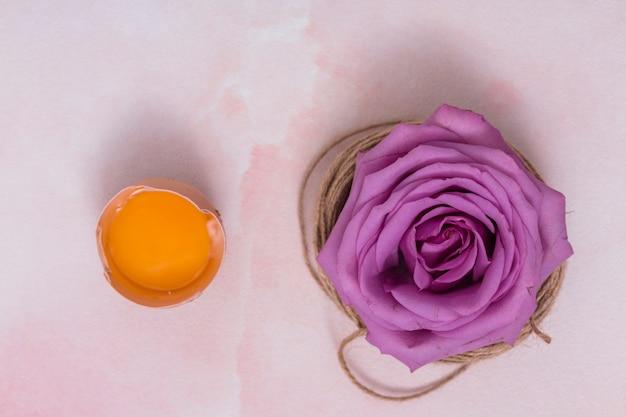 Huevo roto con yema y flor.