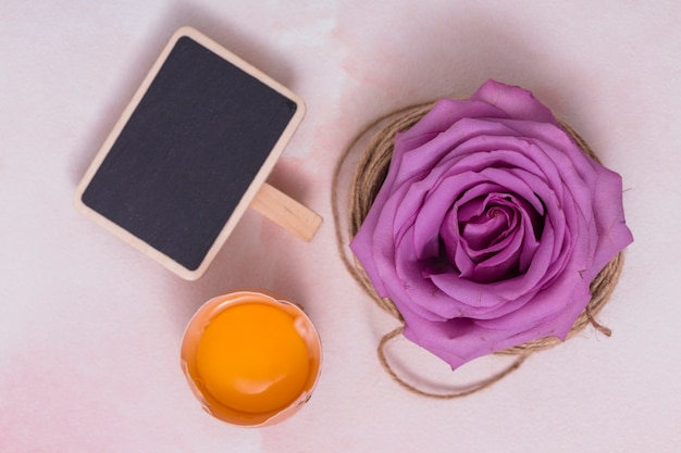 Huevo roto con yema, pizarra y flor.