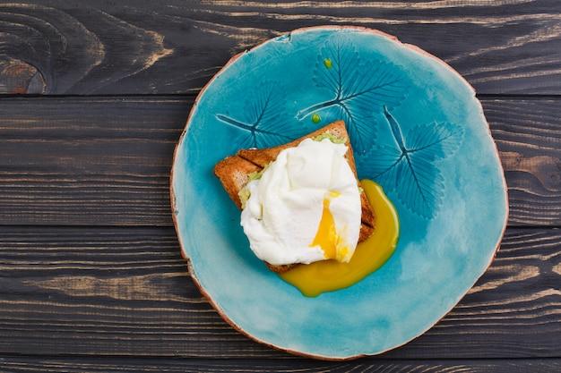Huevo tostado y escalfado con aguacate en un plato en mesa de madera