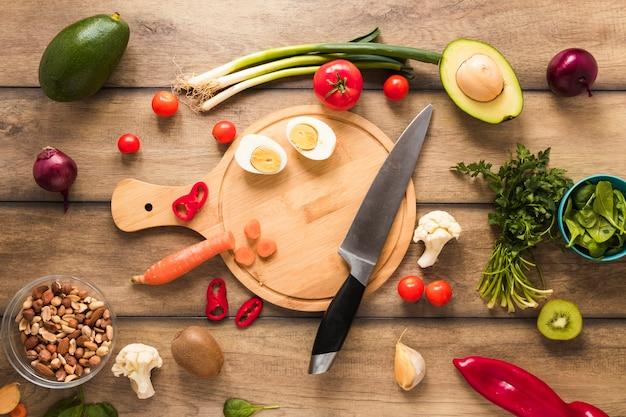 Huevo; verduras e ingredientes frescos con cuchillo en mesa de madera