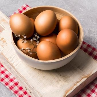 Huevos de alto ángulo y flor en un tazón