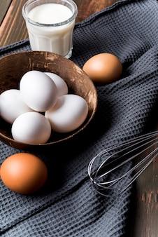 Huevos de alto ángulo y vaso de leche