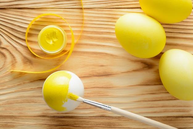 Huevos amarillos con un pincel y pinturas sobre una mesa de madera.