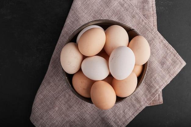 Huevos en una bandeja de madera sobre un paño de cocina, vista superior.