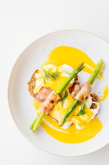 Huevos benedict con espárragos con tocino