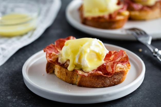 Huevos benedicto: pan inglés tostado, jamón, huevos escalfados con salsa holandesa y limón en gris
