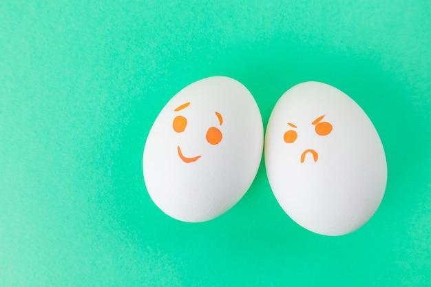 Huevos blancos con caritas pintados con rotuladores. emociones de alegría y enojo.