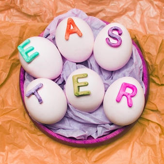 Huevos blancos decorados con letras en bandeja.