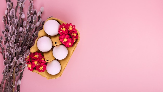 Huevos blancos en estante con flores y ramas de sauce.