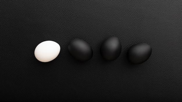 Huevos blancos y negros sobre una mesa oscura