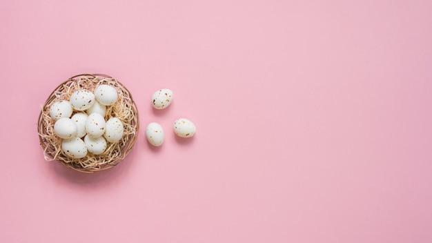 Huevos blancos en nido en mesa