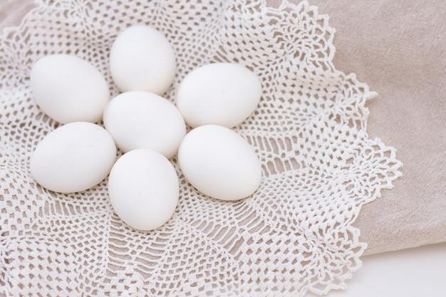Huevos blancos orgánicos de frescura de pollo nutrición saludable en una bolsa marrón y una hermosa servilleta blanca tejida en forma de flor.