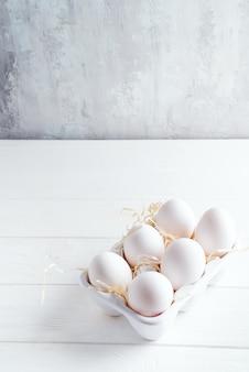 Huevos blancos orgánicos del pollo en caja decorativa de la porcelana en blanco. comida sana natural y concepto orgánico.