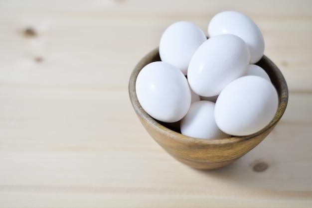 Huevos blancos plateמ plato de madera sobre fondo de madera