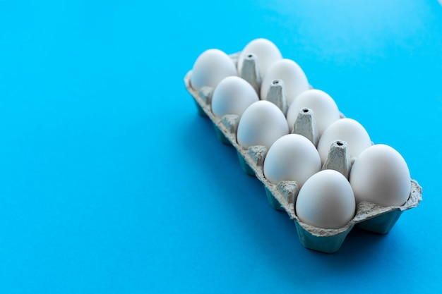 Huevos blancos del pollo en una caja de cartón abierta en un fondo azul. una docena de huevos en envases ecológicos.