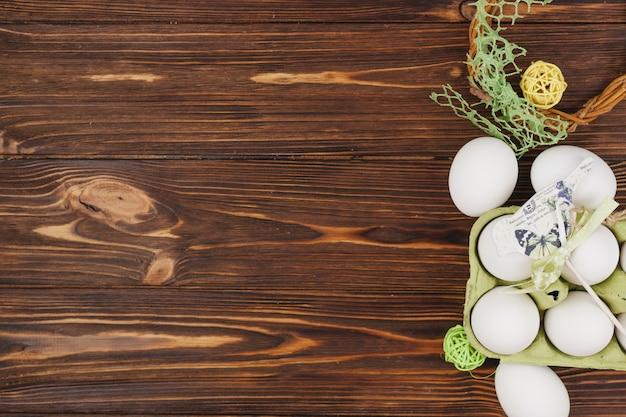Huevos blancos en rack con pajarito en mesa