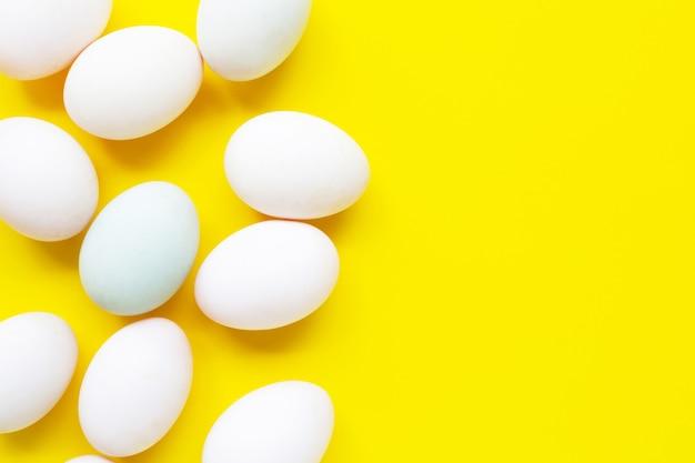 Huevos blancos sobre amarillo.