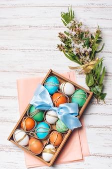 Huevos brillantes en una caja en papel artesanal rosado cerca de un montón de plantas