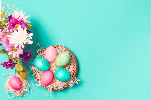 Huevos brillantes en un plato cerca del ramo de flores