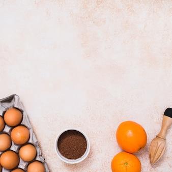 Huevos en caja; polvo de cacao; cítricos y exprimidor de jugos de madera sobre fondo de concreto