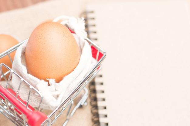 Huevos en carrito rojo con papel marrón en blanco.
