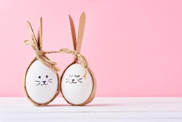 Huevos caseros divertidos con las caras en un fondo rosado. pascua o feliz pareja concepto