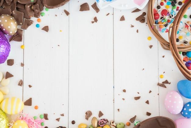 Huevos de chocolate de pascua con caramelos en mesa de madera