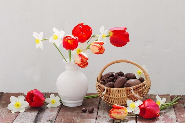 Huevos de chocolate de pascua en cesta y flores de primavera en la mesa de madera vieja