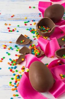 Huevos de chocolate de pascua, cinta rosa y dulces multicolores de pascua en la superficie de madera blanca vieja