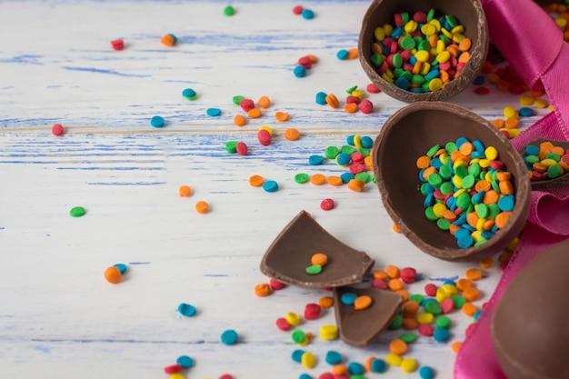 Huevos de chocolate de pascua, cinta rosada, dulces multicolores en la superficie de madera blanca vieja. concepto de pascua