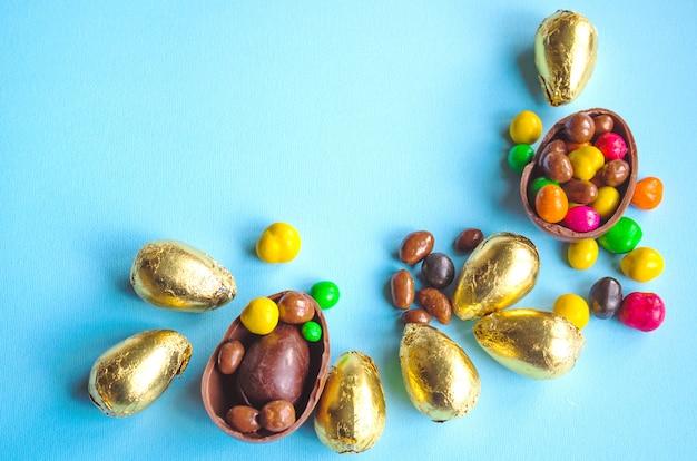Huevos de chocolate de pascua envueltos en papel dorado sobre fondo azul