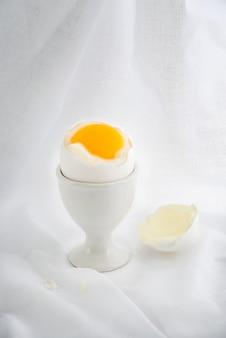 Huevos cocidos y cáscara en taza, sobre tela blanca.