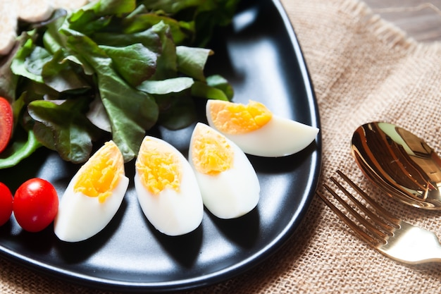 Huevos cocidos en rodajas y verduras en placa negra