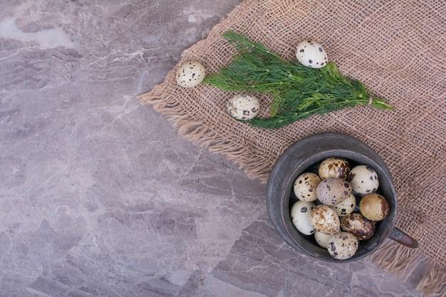 Huevos de codorniz en una olla metálica sobre la arpillera