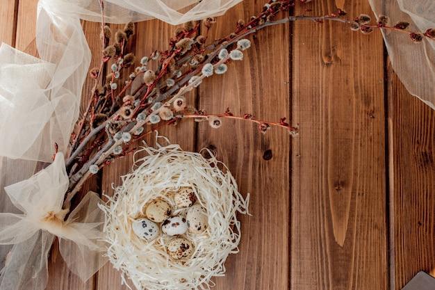 Huevos de codorniz de pascua en nido y rama de sauce sobre un fondo de madera, espacio de copia